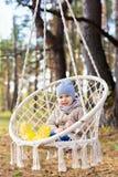 3 anos de criança idosa que balança em uma cadeira de suspensão fora fotos de stock