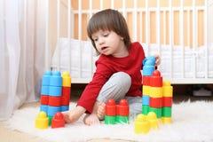2 anos de criança que joga blocos do plástico em casa Fotos de Stock