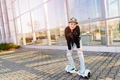 10 anos de equitação velha da menina no auto que equilibra o skate bonde Fotografia de Stock