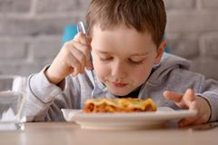 7 anos de lasanha velha comer do menino na sala de jantar Foto de Stock