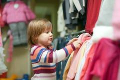 2 anos de menina escolhem o vestido na loja Imagens de Stock