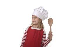 7 anos de menina idosa em cozinhar o chapéu e o avental vermelho que jogam a colher guardando feliz de sorriso do cozinheiro Foto de Stock Royalty Free