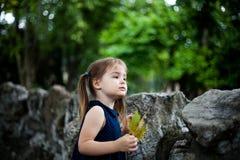 3 anos de menina idosa em um jardim zoológico com uma folha em uma mão Fotografia de Stock