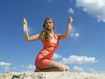 20 anos de menina idosa espalham a areia através dos dedos Foto de Stock