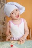3 anos de menina idosa no papel do cozinheiro Fotos de Stock Royalty Free
