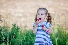 3 anos de menina idosa que come morangos Imagens de Stock
