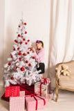 8 anos de menina idosa que decora a árvore de Natal em casa Imagem de Stock