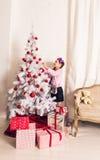 8 anos de menina idosa que decora a árvore de Natal em casa Fotos de Stock