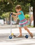 4 anos de menina idosa que fica com 'trotinette' Imagem de Stock Royalty Free