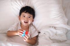 3 anos de menino asiático bonito pequeno idoso em casa na cama, encontro da criança Imagem de Stock Royalty Free
