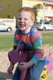 5 anos de menino feliz redheaded idoso que senta-se em uma balancê e em um sorriso imagem de stock royalty free