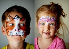 6 anos de menino idoso com olhos azuis enfrentam a pintura de um gato ou de um tigre Menina de olhos azuis consideravelmente emoc Imagens de Stock Royalty Free