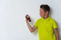 12 anos de menino idoso que faz o bíceps exercitam, copyspace Imagens de Stock Royalty Free
