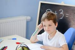 7 anos de menino idoso que faz seus trabalhos de casa Imagens de Stock