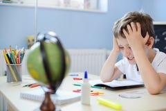 7 anos de menino idoso que faz seus trabalhos de casa Imagens de Stock Royalty Free