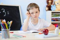 7 anos de menino idoso que faz seus trabalhos de casa Fotografia de Stock Royalty Free