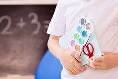 7 anos de menino idoso que guarda acessórios da escola em sua mão Imagem de Stock Royalty Free