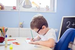 7 anos de menino idoso resolvem a tabela de multiplicação em seu caderno Imagens de Stock