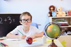 7 anos de menino idoso resolvem a tabela de multiplicação em seu caderno Imagem de Stock