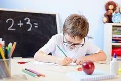 7 anos de menino idoso resolvem a tabela de multiplicação em seu caderno Imagem de Stock Royalty Free