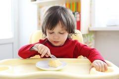 2 anos de menino na camisa vermelha que come a omeleta Imagens de Stock
