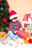 2 anos de menino no chapéu de Santa com presente Fotos de Stock