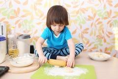 2 anos de menino que aplaina a massa que senta-se em uma cozinha da tabela em casa Fotos de Stock
