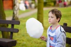 7 anos de menino que come o floss dos doces no parque Imagem de Stock