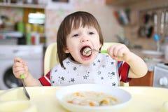 2 anos de menino que come a sopa com bolas de carne Foto de Stock
