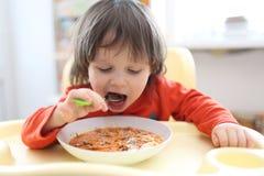 2 anos de menino que come a sopa da vermelho-beterraba da sopa Fotografia de Stock Royalty Free