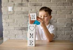 6 anos de menino que guarda o jogo de tijolos de madeira com as letras que fazem a casa da palavra Foto de Stock Royalty Free
