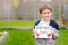 7 anos de menino que guarda um cartão para sua mãe Foto de Stock