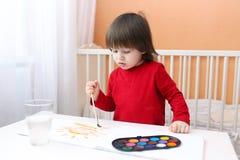 2 anos de menino que pinta em casa Fotos de Stock