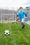 7 anos de menino que retrocede a bola no jardim Fotografia de Stock
