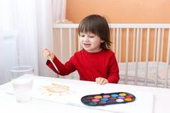 2 anos de pintura da criança com pinturas da cor de água Imagens de Stock Royalty Free
