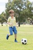 Anos do futebol de jogo feliz de apreciação velho do futebol da criança 7 ou 8 no campo do parque da cidade da grama que corre e  Imagens de Stock