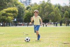 Anos do futebol de jogo feliz de apreciação velho do futebol da criança 7 ou 8 no campo do parque da cidade da grama que corre e  Foto de Stock