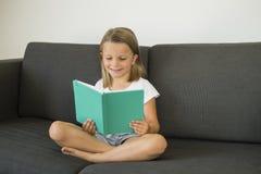 Anos doces e felizes novos do assento da menina 6 ou 7 no sofá home do sofá da sala de visitas que lê um silêncio do livro e ador Imagem de Stock