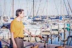 40 anos elegantes do desportista idoso que está na frente dos barcos mo Imagens de Stock Royalty Free