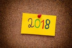 2018 anos escritos na nota de papel amarela na placa da cortiça Imagens de Stock Royalty Free