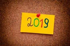 2019 anos escritos na nota de papel amarela na placa da cortiça Imagem de Stock Royalty Free