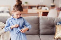 5 anos felizes adoráveis da menina idosa da criança que verifica a curva em sua camisa da forma Fotos de Stock Royalty Free