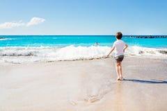 7 anos felizes da criança do menino que joga na praia Imagem de Stock