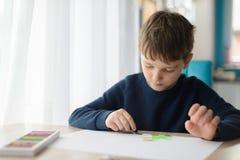 8 anos felizes da criança do menino que tira um cartão para sua avó Fotos de Stock Royalty Free