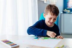 8 anos felizes da criança do menino que tira um cartão para sua avó Foto de Stock Royalty Free