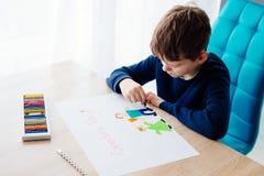 8 anos felizes da criança do menino que tira um cartão para sua avó Imagem de Stock Royalty Free