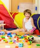 4 anos felizes da criança que joga com brinquedos Imagens de Stock