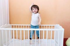 2 anos felizes da criança que salta na cama branca Fotos de Stock Royalty Free