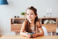 5 anos felizes da menina idosa da criança que come o café da manhã em casa na manhã Fotos de Stock Royalty Free