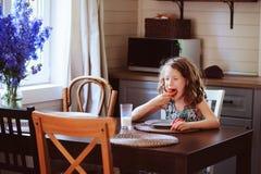 8 anos felizes da menina idosa da criança que come o café da manhã na cozinha do país Imagem de Stock